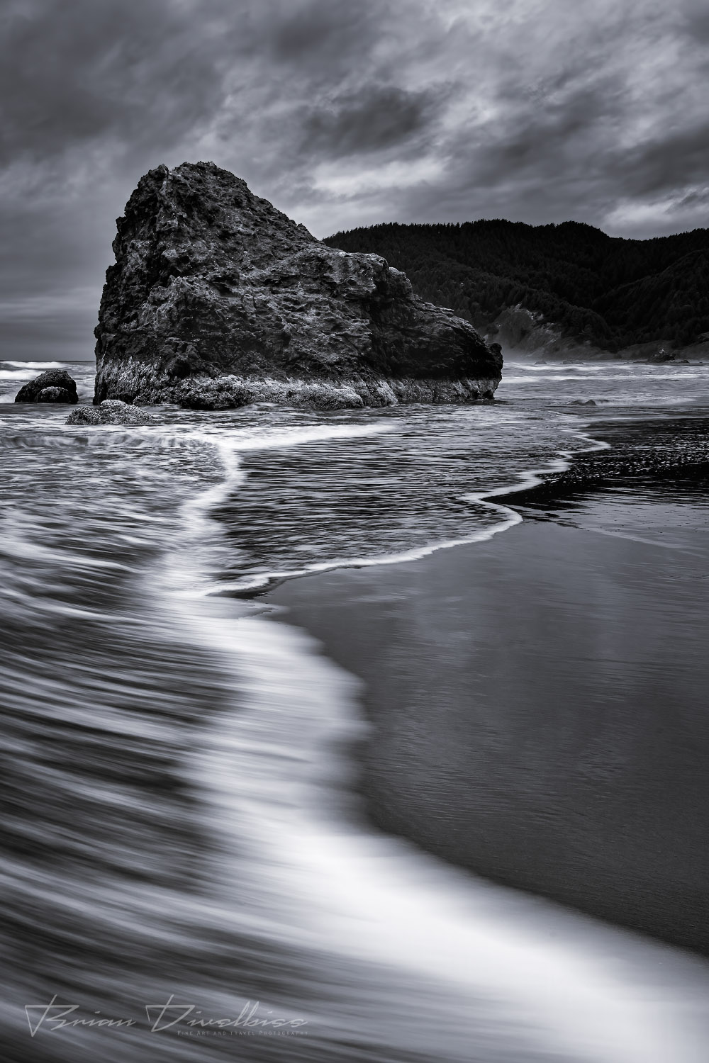 Water surrounds seastacks on the beach in Southern Oregon in black and white.