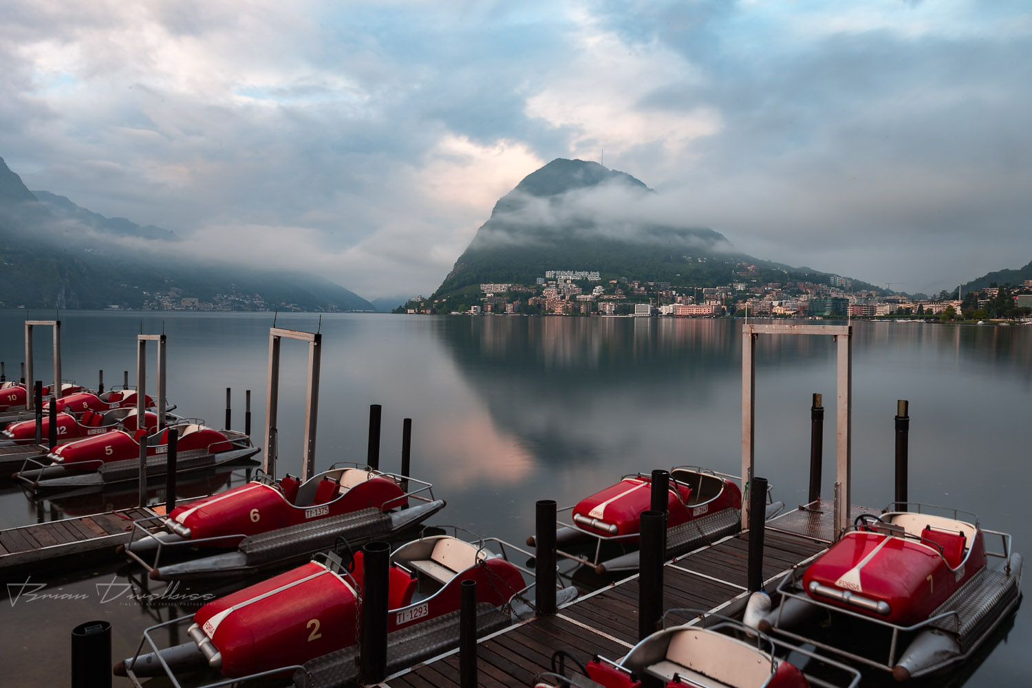 Dock of paddleboats on Lake Lugano with Monte San Salvatore in background in Ticino, Switzerland.