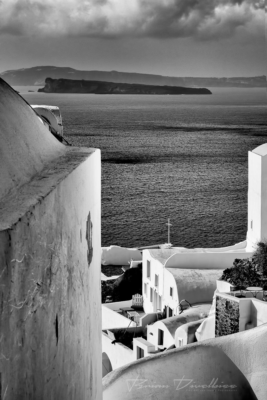 Aegean Sea between buildings of Oía, Santorini in black and white.