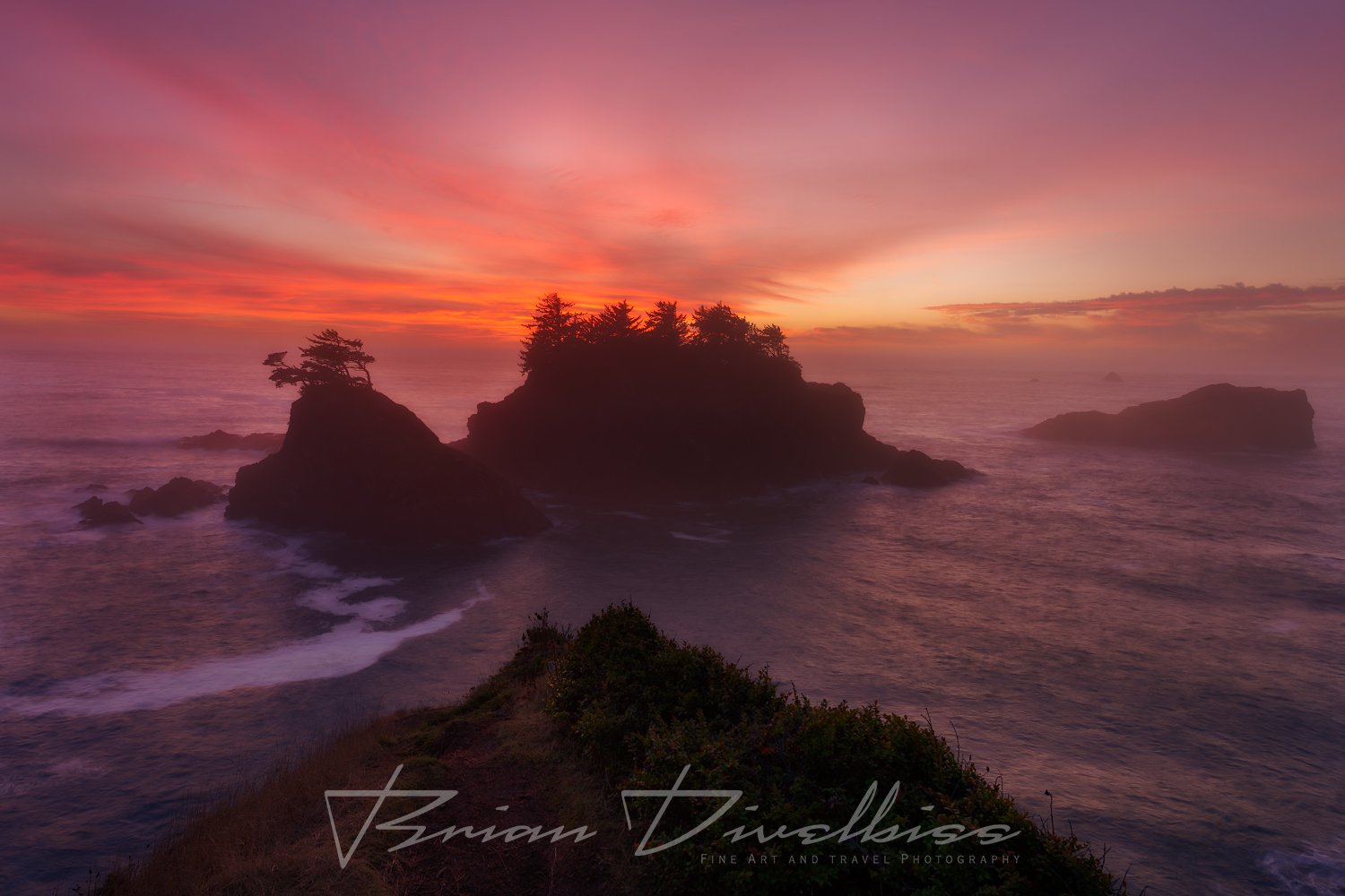 A stunning sunset with hues of purple and red arises from behind a series of seastacks off the rugged coast of Southern Oregon.