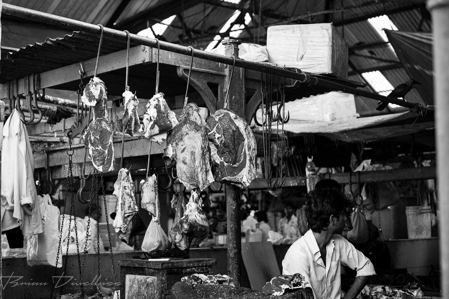 Meat hanging over butcher shop at Crawford Market in Mumbai, India in black and white.
