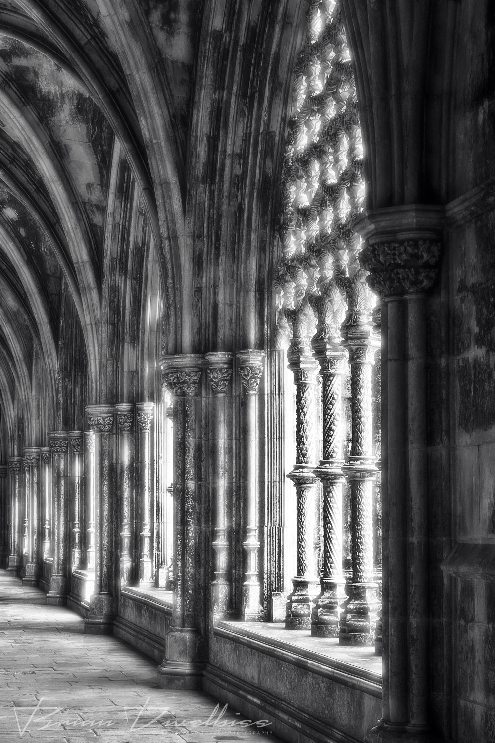 Light coming in through intricate stone arches along pathway in the Royal Cloister of the Monastery of Saint Mary of the Victory in Batalha, Portugal in black a
