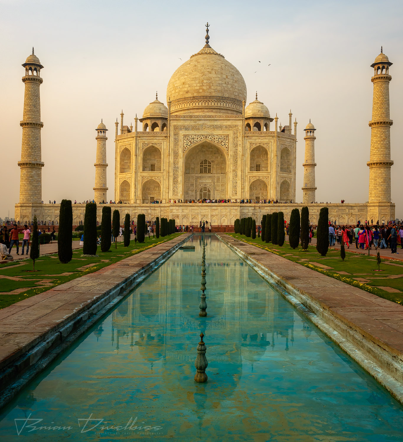 A frontal view of the Taj Mahal over the reflecting pool at dusk.