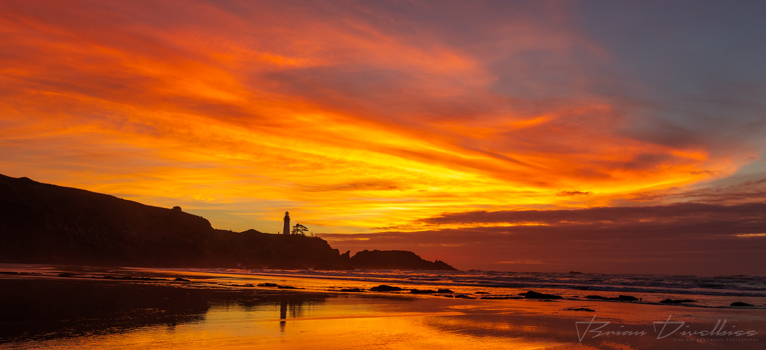 Brilliant sunset with yellow and orange clouds with a silhouette of Yaquina Head lighthouse taken from Starfish Cove, Oregon.